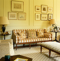 A mahogany banquette upholstered in brown and white check forms the focus point of this traditionally furnished panelled drawing room