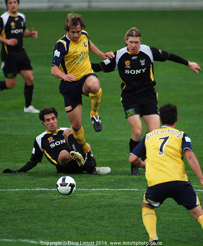 Mariners' Dylan Macallister and Phoenix's Karl Dodd chase the ball past the grounded Daniel Cortes toward John Hutchinson.<br /> A-League Football. Wellington Phoenix v Central Coast Mariners at Westpac Stadium, Wellington. Sunday, 20 July 2008. Photo: Dave Lintott / lintottphoto.co.nz