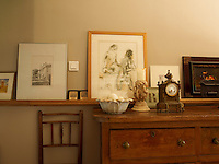 A picture rail is put to its original use displaying a collection of drawings and paintings