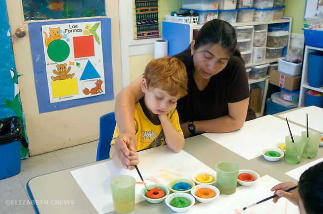 Berkeley CA  Aide helping student paint in bilingual Spanish-English preschool.