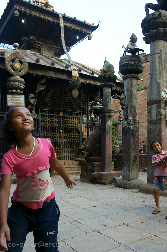 girl playing in front of a temple in a backyard area Bhaktapur,Nepal