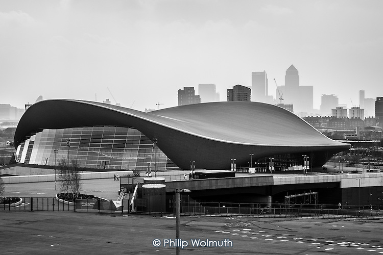 Smog caused by air pollutants mixing with dust from the Sahara obscures the view of Canary Wharf beyond the Aquatics Centre designed by architect Zaha Hadid in the Queen Elizabeth Olympic Park, Stratford.