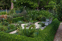 Formal herb garden room with bench and boxwood hedge; in Gamble Garden, Palo Alto, California