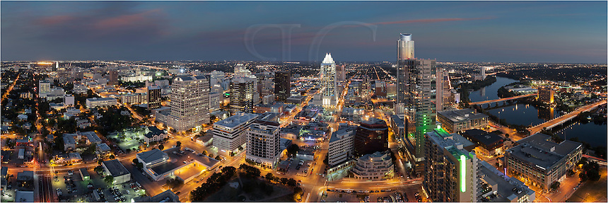 This image of the evening Austin skyline is a 3 image stitch. On the left, you can see the University of Texas Tower. Going from left to right, you can see the Texas State Capitol, the Frost Tower, and Ladybird Lake (Town Lake) that flows in from the Hill Country and Lake Travis. on its east bank sits the Austin City Hall. On its west bank is the Hyatt Hotel flanked by the 1st Street Bridge and Congress Bridge.