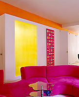 In this bright and colourful New York loft the bedrooms and bathrooms are situated in a partitioned area with the main bathroom behind the yellow Plexiglass panel