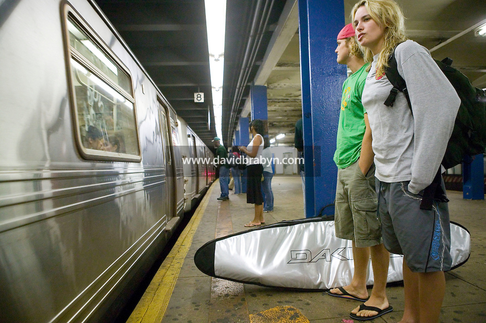 A surfer couple (R) waits for the subway at a station in New York, United States, after a morning surf at Far Rockaway beach, 17 September 2005. Photo Credit: David Brabyn.