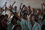 Children raise their hands in class in the Catholic school in Lugi, a village in the Nuba Mountains of Sudan. The area is controlled by the Sudan People's Liberation Movement-North, and frequently attacked by the military of Sudan. The church has sponsored schools and health care facilities throughout the war-torn region.