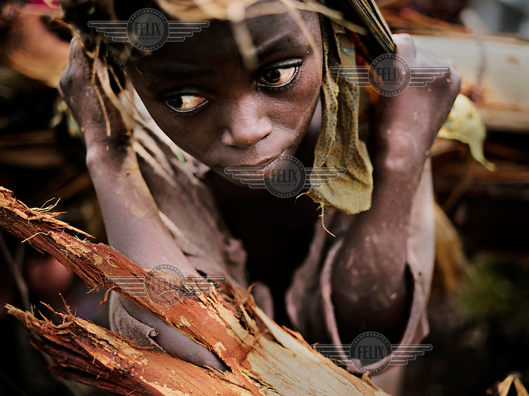 A girl on her way home from the bush with firewood for cooking at a UN IDP camp near Goma. Often kidnapping and sexual assaults on women, and even children, happens when they leave the villages to fetch firewood, water or to do field work..