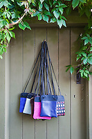 A selection of brightly-coloured leather shoulder bags designed by Matt Fothergill photographed against the  garden gate