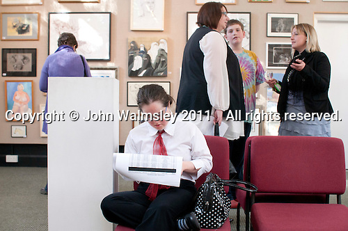 Student (seated) from the Supported Learning group at the opening of an exhibition of students' work, Harvey Gallery, Adult Learning Centre, Guildford, Surrey.