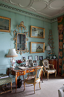 A collection of old and new family photos are displayed on an antique desk in the morning room