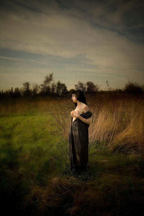 A young woman dressed in grey dress with naked shoulders and dark hair standing between grass in the meadow hiding her naked breat