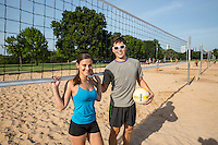 young attractive couple with volleyball on vacation under a clear blue sky on the sand volleyball courts at Zilker Park in downtown Austin, Texas.