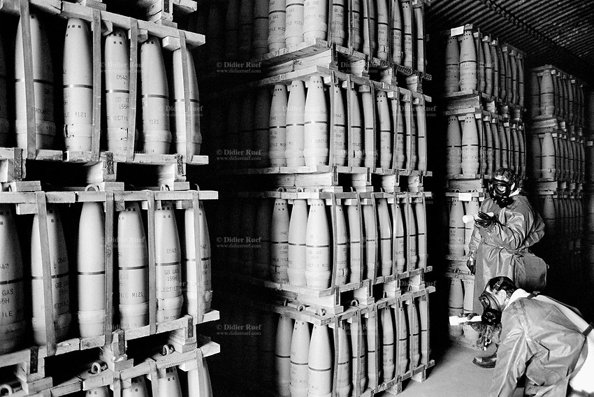 "Usa. Utah. Tooele county. Deseret chemical depot. Two workers, wearing gas masks,boots, protective suits and flashlights, follow the firt entry procedures and look for any leakages in a earth covered igloo which provides secure storage for the weapons. 155 mm GB Nerve Agent, called also "" Sarin"". Tooele chemical agent disposal facility (TOCDF). Program for destruction of chemical weapons and agent. Incinerating plant. Deseret chemical depot is distant 100 km from Salt Lake City. The Deseret Chemical Depot is one of eight Army installations in the U.S. that currently store chemical weapons. The weapons originally stored at the depot consisted of various munitions and ton containers, containing GB and VX nerve agents or H, HD, and HT blister agent. The Tooele Chemical Agent Disposal Facility is designed for the sole purpose of destroying the chemical weapons stockpile located at the depot. © 1998 Didier Ruef"