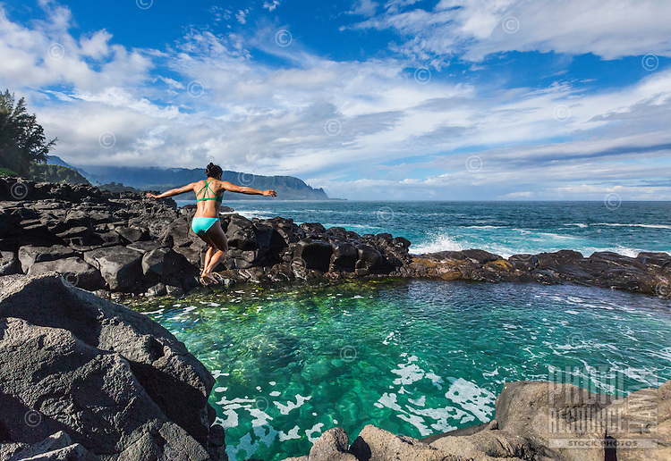 A young woman jumps into the crystal clear water of Queen's Bath, Princeville, North Shore of Kaua'i.A sacred place where visitors must be very careful of the incoming surf!