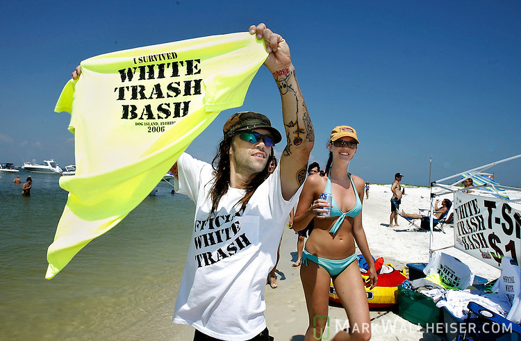 Rob Aaron (L) hawks t-shirts May 28, 2006 on the beach at the 2006 White Trash Bash on the remote Dog Island, off the coast of Carrabelle, FL which is 75 miles south of Tallahassee.  The White Trash Bash has been an annual Memorial Day weekend gathering for the past ten years.  this year's event drew well over 360 boats packed with people celebrating the end of school and the Memorial Day holiday.     (Mark Wallheiser/TallahasseeStock.com)