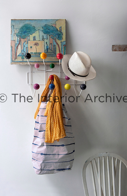 A colourful 1970s coat rack is a feature on the wall of the kitchen