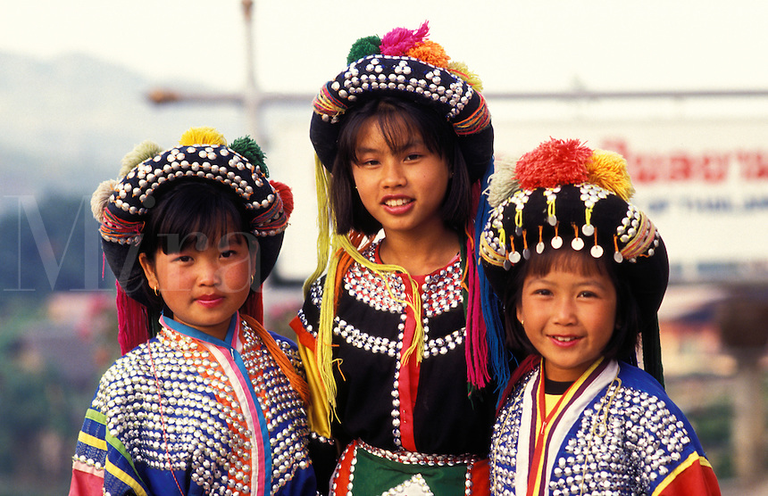 Thailand. Mai Sai in the extreme north, in the Golden Triangle at the northern road crossing into Burma.  Three young girls dressed in a hybrid hill tribe costume pose for tourists for a little extra