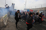 Palestinian women run from tear gas fired by Israeli troops at Qalandia checkpoint between Jerusalem and the West Bank city of Ramallah, Saturday, March 8, 2014. Palestinian women marked International Women's Day by marching to the checkpoint where clashes broke out with Israeli troops. Photo by Issam Rimawi