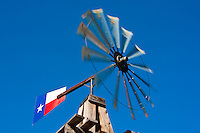 A windmill with a Texas flag and colors, normally equipment found on a farm, mounted in the parking lot of the historic Rogers Hotel in Waxahachie, Texas.