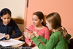 Elementary school Grade 5 arts enrichment female students working together on assigment in music theory class horizontal