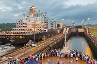 Panama Canal, Panama.  Container Ship Entering First Lock, Caribbean Side, Heading toward Lake Gatun, Passengers on Cruise Liner Watching.