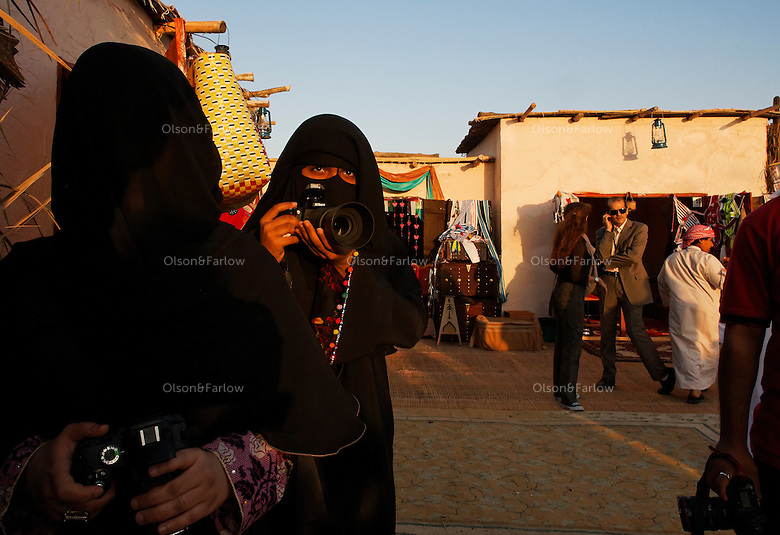 Covered women photographers gather for a view of Sheik Tahnoon Bin Mohamed--Ruler of Alain) arrives at the Souk area of the camel beauty contest with his son Sheik Sultan Bin Tahnoon who is head of ADACH (Abu Dhabi Assoc. of Culture and Heritage) and ADTA Tourist Authority.