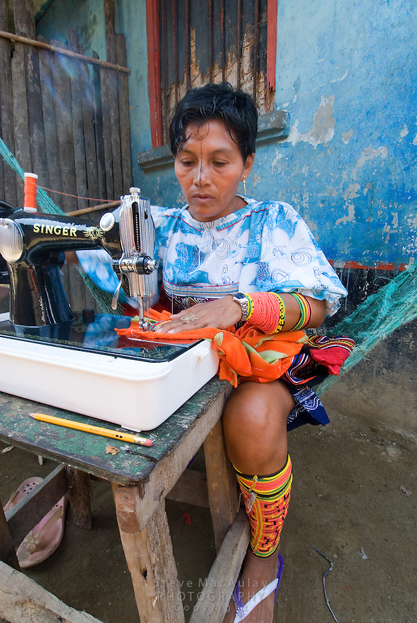 Kuna Indian woman sewing a brightly colored mola on an old Singer sewing machine - Comarca De Kuna Yala, San Blas Islands , Panama