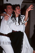 Romania. Young man and woman in traditional embroidered costumes dancing.