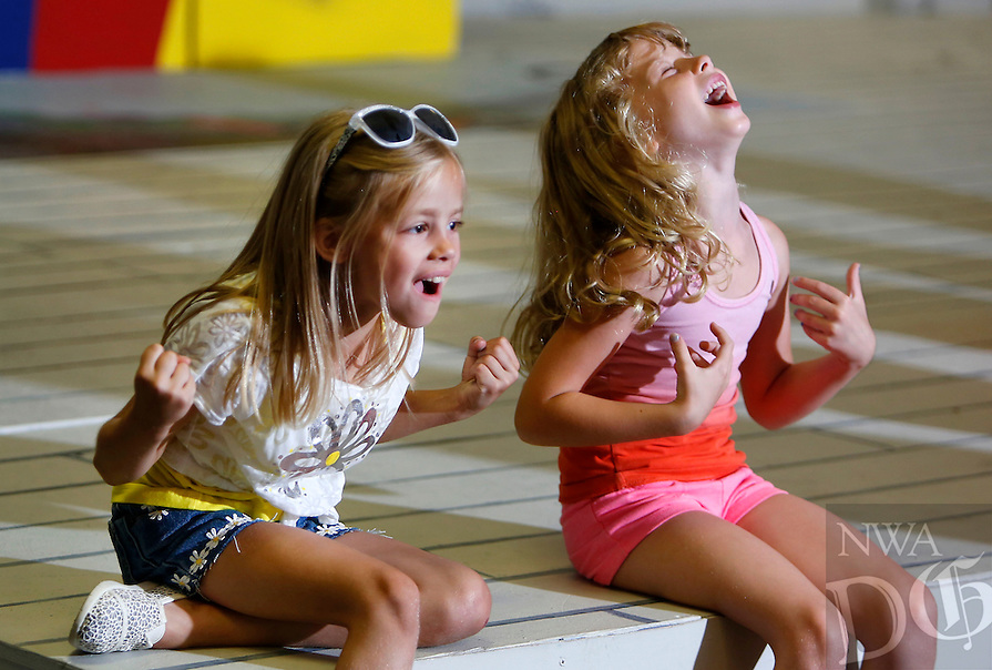 NWA Media/DAVID GOTTSCHALK - 6/27/14 - Macy Guist, left, 7, reacts with other actors including Maysie Church, right, 6, after hearing the news of the pool being closed during their play production Friday June 27, 2014 at Arts Live Theatre in Fayetteville. The actors ages five - seven were participating in a one week Summer Fun Musical Theatre Camp under the instruction of Jules Taylor.