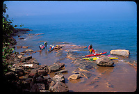 A GROUP OF SEA KAYAKERS ON THE ROCKY SHORE OF SAND ISLAND IN THE APOSTLE ISLANDS NATIONAL LAKESHORE NEAR BAYFIELD WISCONSIN.