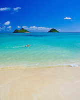 A swimmer cuts through the pristine waters of Lanikai beach.  The Mokulua Islands stand majestically in the background