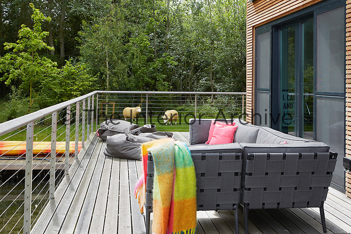 A decked terrace is a perfect spot to relax on sunny days. Bright pink cushions and woollen throws add spots of vibrant colour.