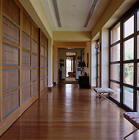 The polished wooden floors of a corridor where a series of panelled sliding screens leads to the living area