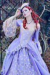 Pretty, sweet looking young woman with red hair wearing a fancy purple gown with lace