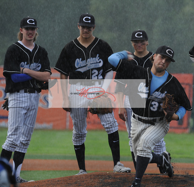 In a downpour, relief pitcher Sam Hanson warms up as Cody Curfman, Charlie Bucolo and Matthew Hess look on.