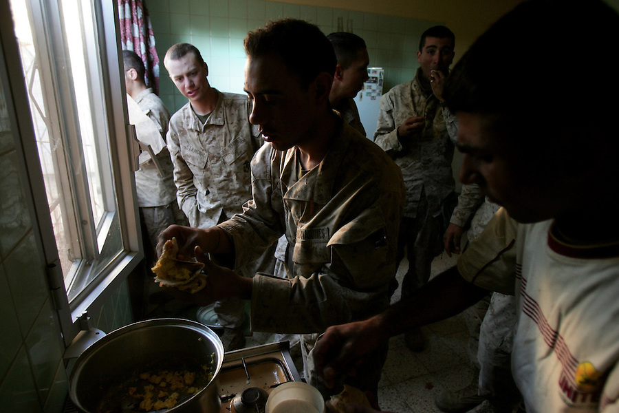 US Marines and Iraqi soldiers cook in a commandeered home in Ubaydi during Operation Steel Curtain on Tues. Nov. 15, 2005.
