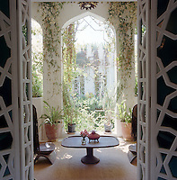 Intricately patterned doors open onto a terrace with a series of arches framing an inner courtyard