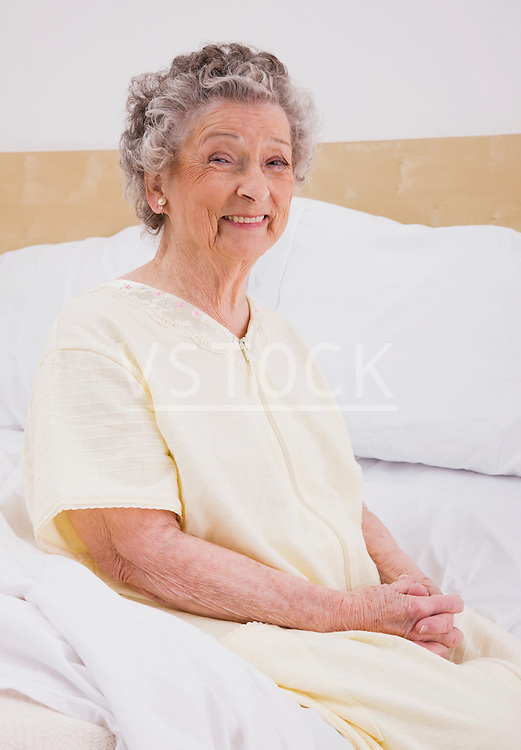 Senior woman sitting on bed, portrait