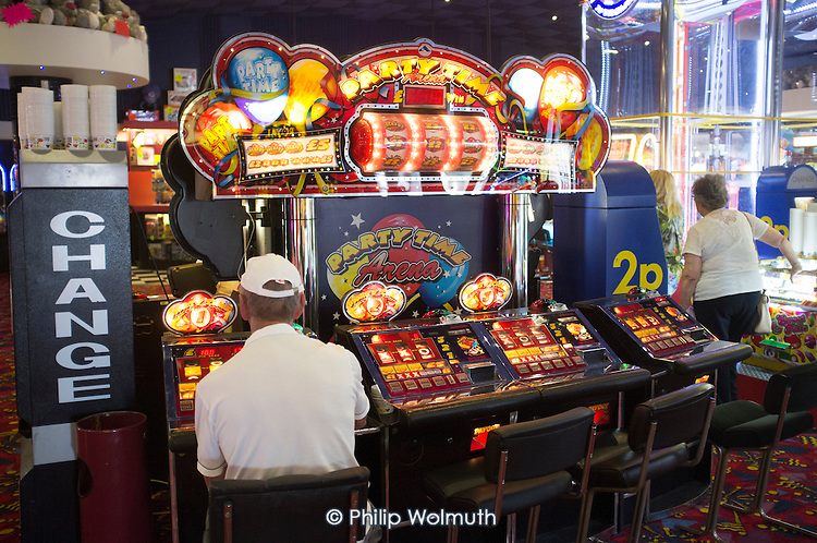 Man at a slot machine on Clacton Pier.  The resort is the second most deprived seaside town in the UK.