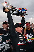 Mar 29, 2014; Las Vegas, NV, USA; Hoisting up her trophy, NHRA pro stock driver Erica Enders-Stevens celebrates after winning the K&N Horsepower Pro Stock Challenge during qualifying for the Summitracing.com Nationals at The Strip at Las Vegas Motor Speedway. Mandatory Credit: Mark J. Rebilas-