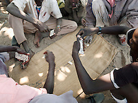 Men of the Nuba tribe sitting playing dominoes in Nyaro village, Kordofan region, Sudan