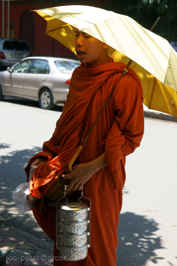 monk with umbrella asks for donation, Phnom Penh, Cambodia, August 2011