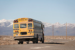 A school bus drives a rural highway at the end of the school day in rural Nevada