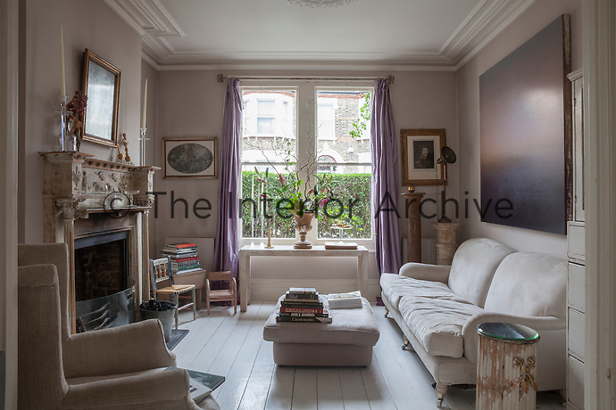 The purple hues of the abstract painting and curtains bring a subtle introduction of colour to the paler, taupe tones of the living room