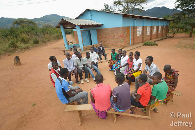 Members of a youth sexual and reproductive health club hold a meeting outside a Catholic church in Kacheche, Malawi. With assistance from the AIDS program of the Livingstonia Synod of the Church of Central Africa Presbyterian, club members educate their peers about avoiding HIV transmission, resisting early marriages, and the prevention of school dropouts.