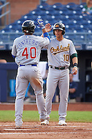 Mesa Solar Sox catcher Willson Contreras (40) high fives Chad Pinder (10) after hitting a home run during an Arizona Fall League game against the Peoria Javelinas on October 21, 2015 at Peoria Stadium in Peoria, Arizona.  Peoria defeated Mesa 5-3.  (Mike Janes/Four Seam Images)