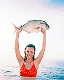 FIJI, Northern Lau Islands, a smiling young woman holds up a travail fish