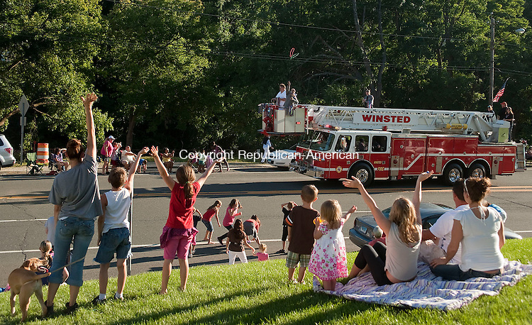 WINSTED, CT-18 AUGUST 2012--081812JS11- Parade goers wave to the Winsted ladder truck as members of the department throw beads to the crowd during the Winsted Fire Department's  annual parade down Main Street in Winsted on Saturday. The department is celebrating its 150th year. .Jim Shannon Republican-American