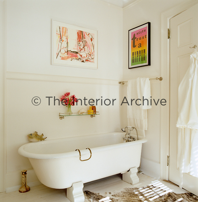 A work on paper by Cecily Brown and a letter press by Scott King hang above the vintage roll-top bath in this all-white bathroom